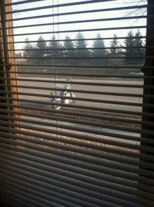 Parked motorcycle seen through window blinds